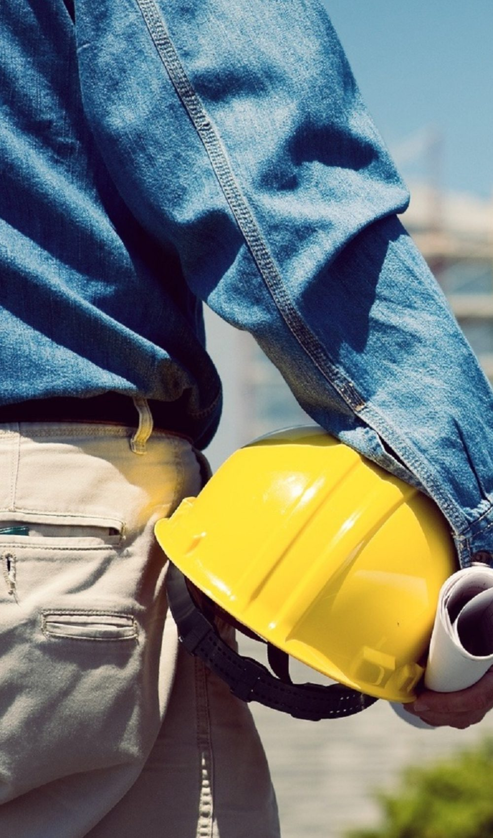 A construction worker or foreman at a construction site observing the progress of construction job or project, with copy space